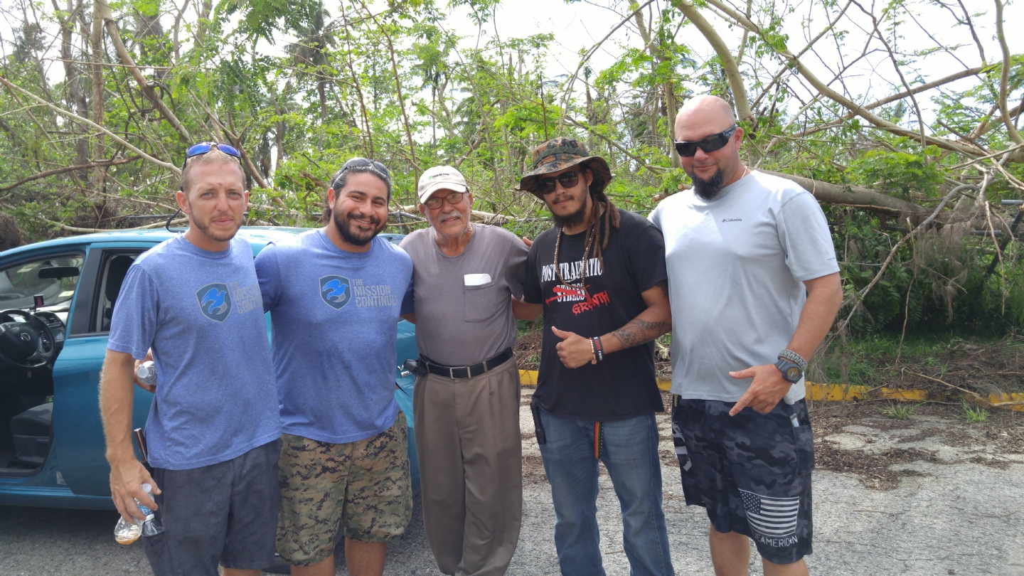 The photo was taken by Post 754 Commander Rosa on his second day of our Puerto Rico support mission on Wednesday, October 18th 2017. Commander Rosa and Anasco VFW Post 11103 Senior Vice Commander Carlos Rodriguez were finishing up their assessment of damages to the Post and two guys came up, introduced themselves as Mike (Army Veteran on the right) and Nesky (Marine Veteran with boonie cap) from Warfighter DRT (Disaster Relief Team). They had been trying to find a contact for the Post to help with the grounds cleanup. Shortly after, two more guys showed up, Edwin (Marine Veteran second in the picture) and James (First Responder; far right). They spoke for several minutes coming up with a plan for grounds cleanup and they invited Commander Rosa to their base-camp (Villas de Anasco), which was located across the street and since that day Commander Rosa stayed with them until his return in January.