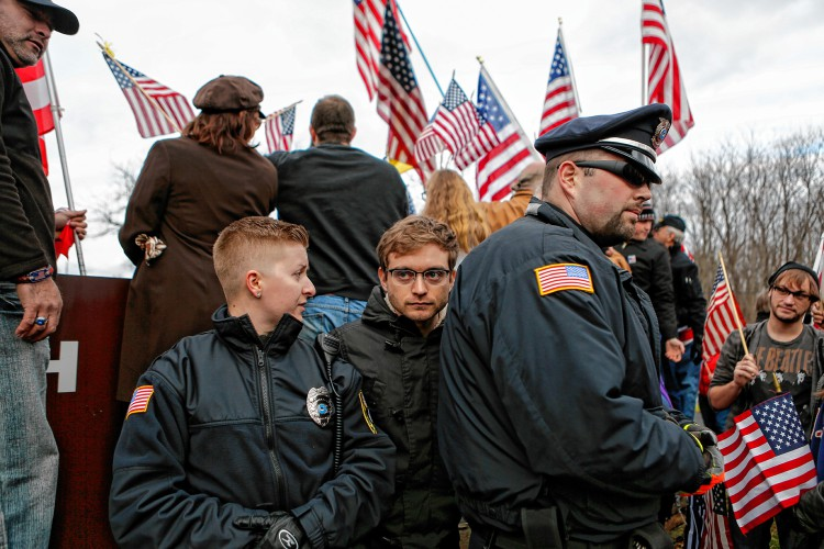 Campus police Kate Godfrey, left, and Matt Brown form a barrier around a Hampshire College student, center, who sat in front of the school's sign while protesters were trying to take a photo there. The Nov. 27, 2016 protest decried Hampshire's decision to hold off on hoisting the flag in the center of the Amherst campus. The school removed the U.S. flag indefinitely after, since Election Day, it has been set ablaze, replaced, and lowered to half-staff. —GAZETTE STAFF/SARAH CROSBY